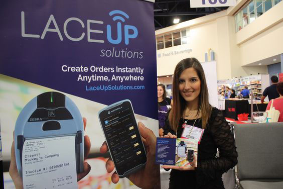 Girl from the LaceUp team stand beside a LaceUp Solutions' poster at the 19th Americas Food and Beverage Show & Conference